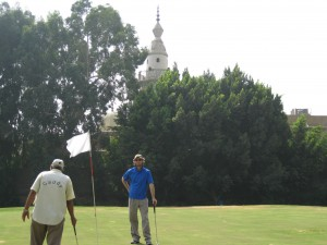 Glen and Caddy on green with Mosque in the background.