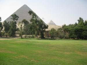 Both great Giza Pyramids behind the green.